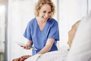 nurse helping patient with tablet